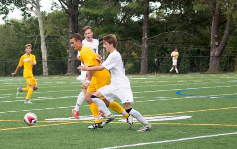 Varsity soccer midfielder Seth Anderson fights for the ball against a Loyola player on Sep 16. The varsity soccer team finished their season with a 6-13-2 record.