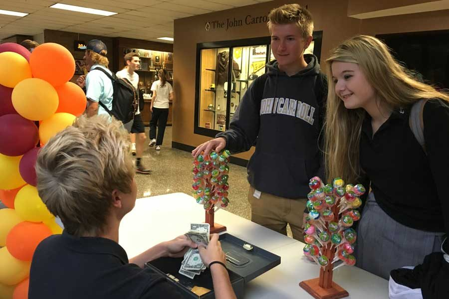 Future Business Leaders of America member sophomore Nick Lukas sells gourmet lollipops to seniors Max Moxey and Jesseca Dunnet. FBLA sold lollipops on Oct. 27 and Oct. 28 as a fundraiser for competitions and field trips.