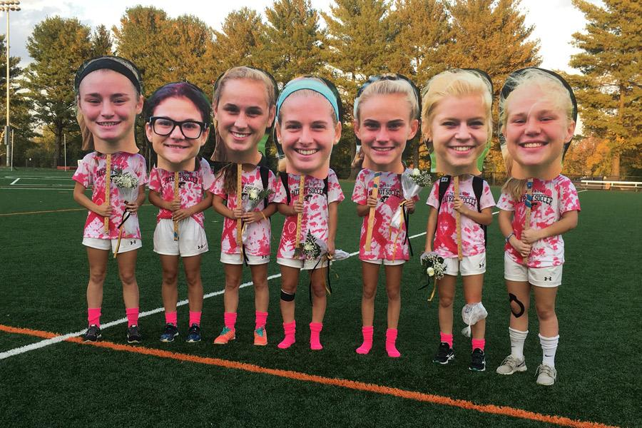 Seven women's soccer seniors pose with their fatheads after their senior game against Mercy on Oct. 19. Women's soccer is one of the varsity teams that emphasizes team unity on and off the field.