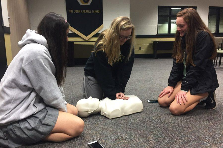 Senior Shelby Umbarger practices CPR while seniors Claire Amato (left) and Brooke Hare (right) observe her. Head Athletic Trainer Erik Fabriziani held a CPR training session in the Brown Room on Wednesday, Nov. 30 for all seniors who are leaving the country for their Senior Project.