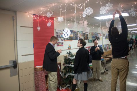 Students put up decorations  for the John Carroll holiday door decorating contest. This contest is a tradition that many students enjoy.