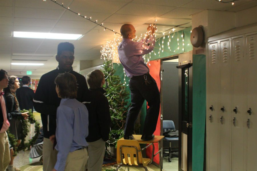 Social studies teacher Jacob Hollin stands on a chair to hang Christmas lights above the door of his advisory as part of the FCA Door Decorating contest. Hollin is one of many advisors who gets excited about door decorating and encourages his students to participate.