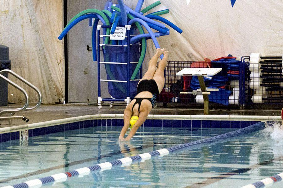 Sophomore Kaelyn James dives off the block at the start of the 100m freestyle. On Wednesday Dec. 7, the women's swim team lost to Roland Park Country School and the men's swim team lost to Archbishop Curley.