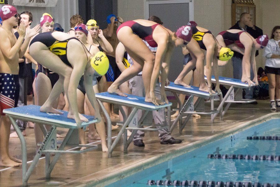 Senior Olivia Barnhart (left) prepares to dive into the pool in the 200m Freestyle relay. Barnhart, along with teammates sophomore Kaelyn James, junior Amelia Wickham,and senior Julianna Richard finished first and won six points for the women's team during the event.