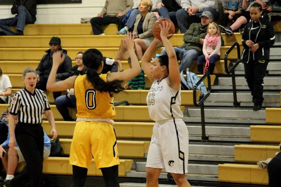 Junior Nikki Hunter holds the ball above her head as she searches for an opponent. Several athletic teams, including the women's basketball team, have used the new film room to watch highlights from the previous game.