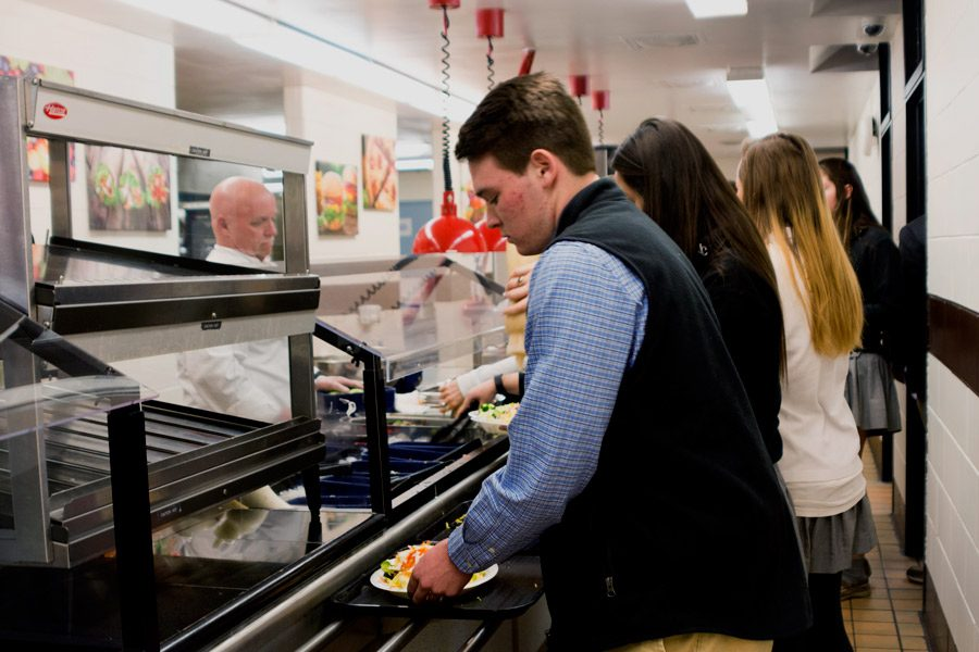 Senior Sam O'Donnell prepares a plate of salad from the salad bar, which was brought back to the cafeteria due to popular demand. On Tuesday, Jan. 24, the Food Committee promoted the return of the salad bar by offering free salads to all students.