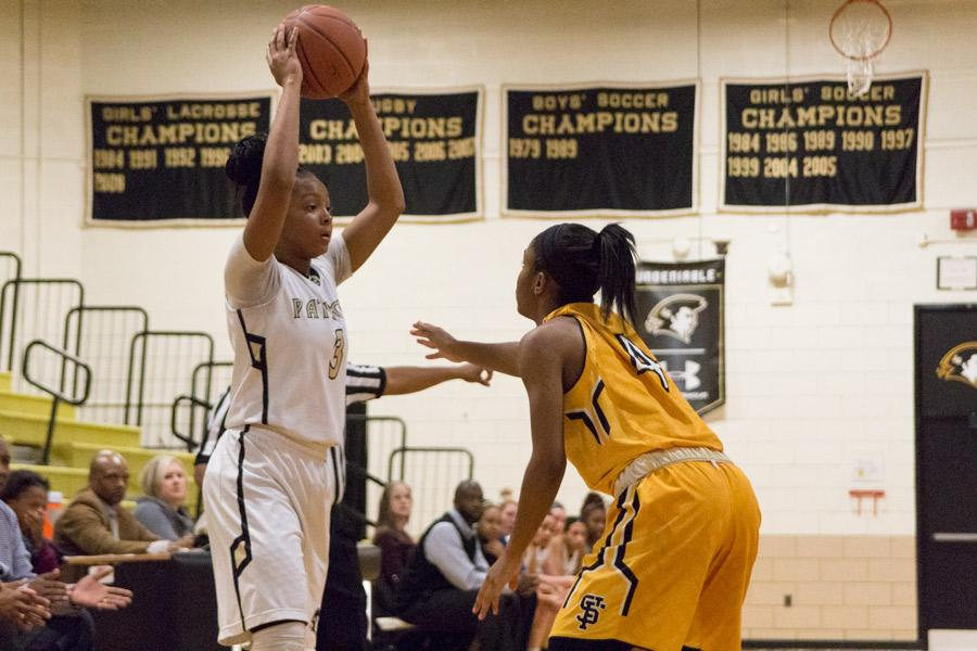 Junior Branyelle Carillo searches for an open teammate to pass the ball to while being closely guarded by an opponent. The women's varsity basketball team was defeated by St. Frances 42-60 on Jan.19.