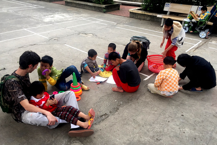 Senior Joe Rayman sits with a group of children at a children's center in Hanoi, Vietnam. Rayman worked at the center for orphans and children with disabilities as a part of his senior project.