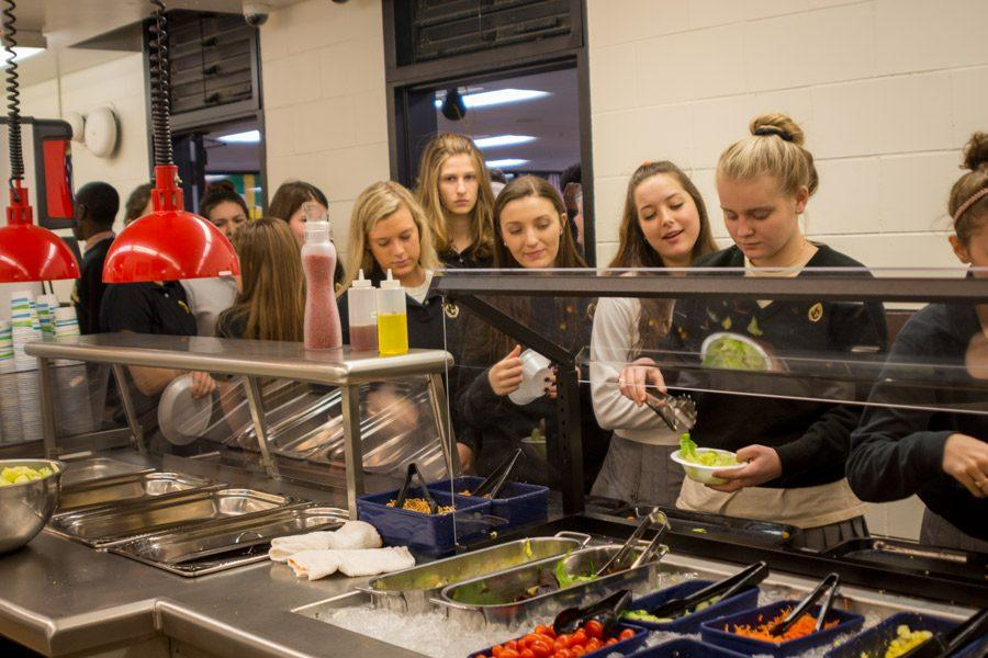 Students wait in line for their turn to fill up a free bowl of salad from the newly reopened salad bar. The return of the salad bar on Tuesday, Jan. 24, was part of an effort by the Food Committee to offer healthier options in the cafeteria.
