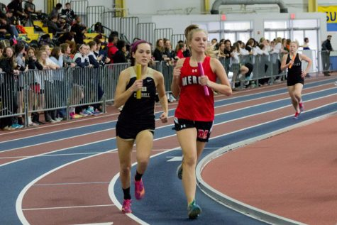 Keeping pace with a Mercy High School runner, junior Laura Amrhein races in the second leg of the 800m relay. The women