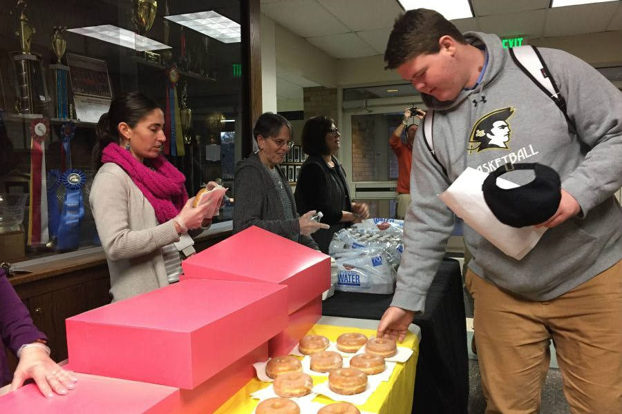 Sophomore Ben Blessing reaches for a donut in front of teachers Courtney Von Lange, Louise Geczy, and Tess Gauthier who assisted with handing out donuts and water bottles in celebration of Student Appreciation Day. On Thursday, Feb. 2, students were recognized  by the school for their effort throughout the year.  Catholic Schools Week also included a Teacher Appreciation Day on Friday, which honored teachers and faculty members, thanking them for their hard work. These two days were a positive  experience for every member of the community.