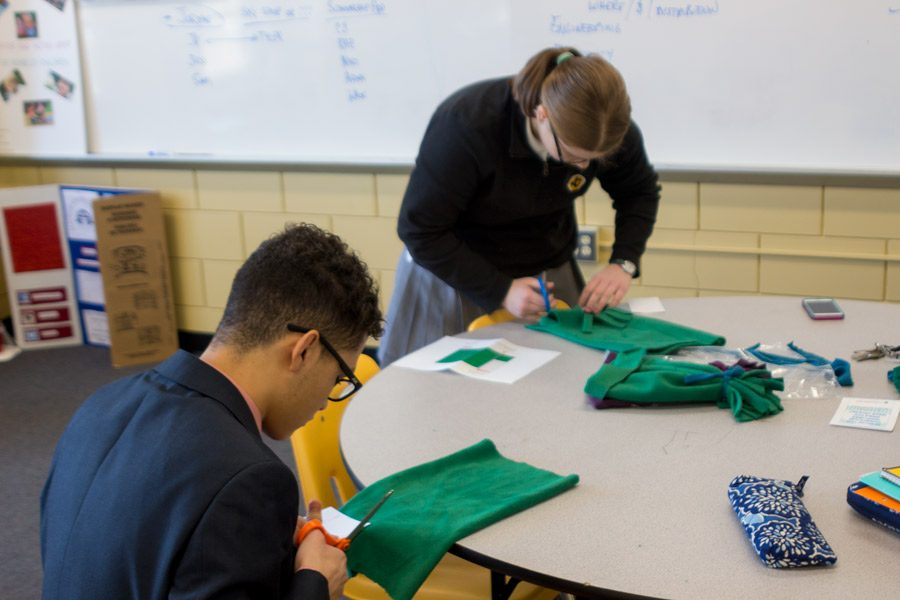 Senior CJ Beteta and sophomore Katie Smith cut out fabric during the H-day period in advisory. After attending grade-level meetings, every advisory made hats for children with pediatric cancer.