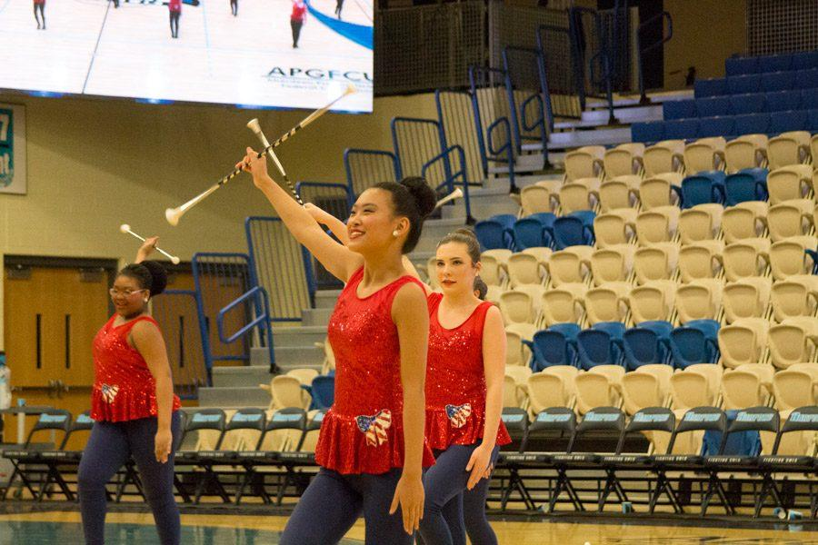 Freshman Angela Boeren swings her baton in the air while marching in place in front of her teammates during a performance on Jan. 18 at Harford Community College. Boeren's baton twirling team, the TwirlTasTix, performed during the halftime of the men's basketball game.