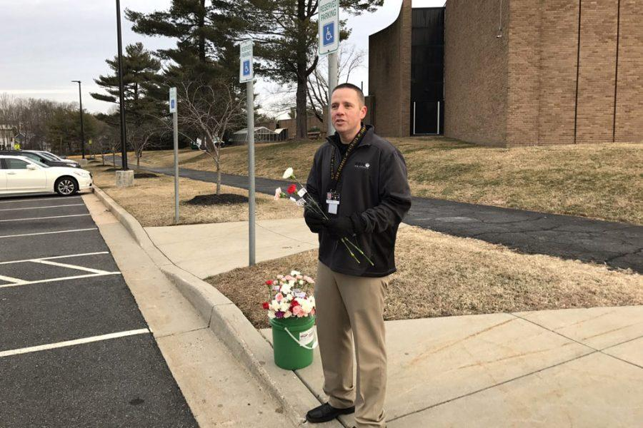 Director of Advancement Todd Sullivan waits for parents at the teacher parking lot to give them a flower in honor of Valentine's Day. Students were also given flowers during their advisories which were sent to them by their peers through the National Honors Society.
