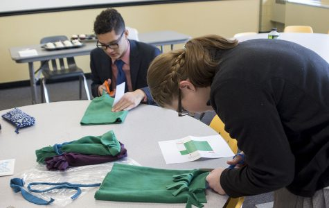 Senior CJ Beteta and sophomore Katie Smith cut fabric in order to make hats for pediatric cancer patients. The hats were made during the H-day assembly mod after each grade level attended their respective meetings.