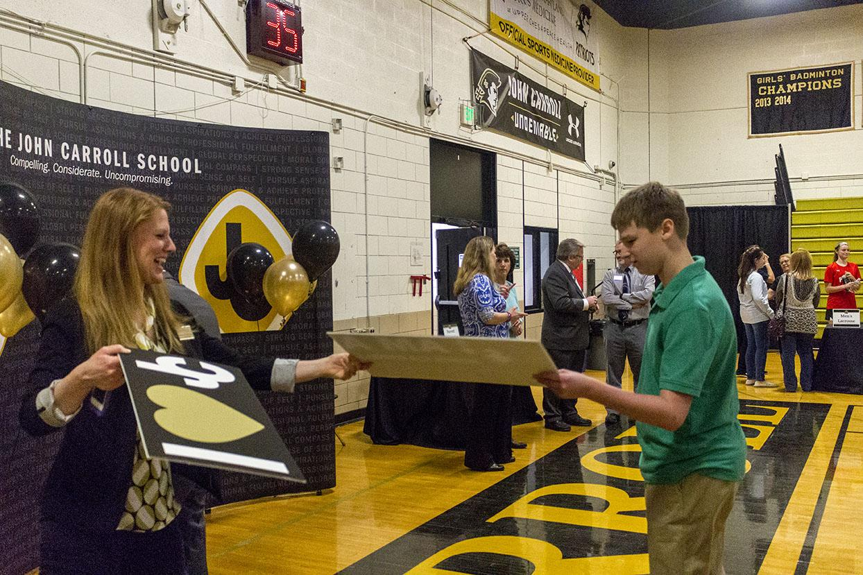 Enrollment assistant Susan Roarty hands a photo prop to a prospective student at A Closer Look.  A Closer Look was held on Thursday, Feb. 23 from 6 p.m. to 8 p.m. to give admitted students a final look at the school.