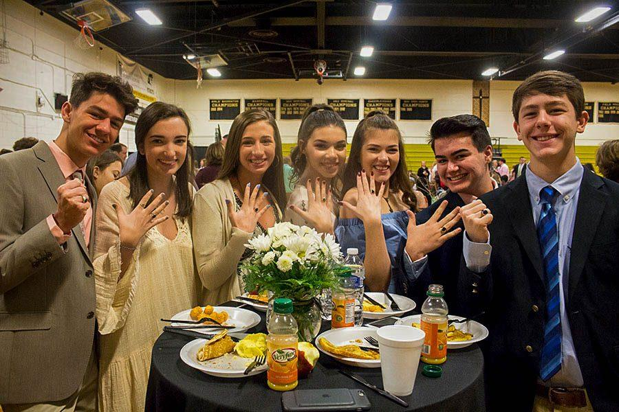 Juniors Joey Ishak, Josephine Cohen, Karson Langrehr, Ella Wilson, Teresa Langbein, Chris Cerra, and Kyle Wedemeyer (left to right) pose with their rings at the junior ring breakfast. The breakfast took place on the morning of March 24 in the Upper Gym.