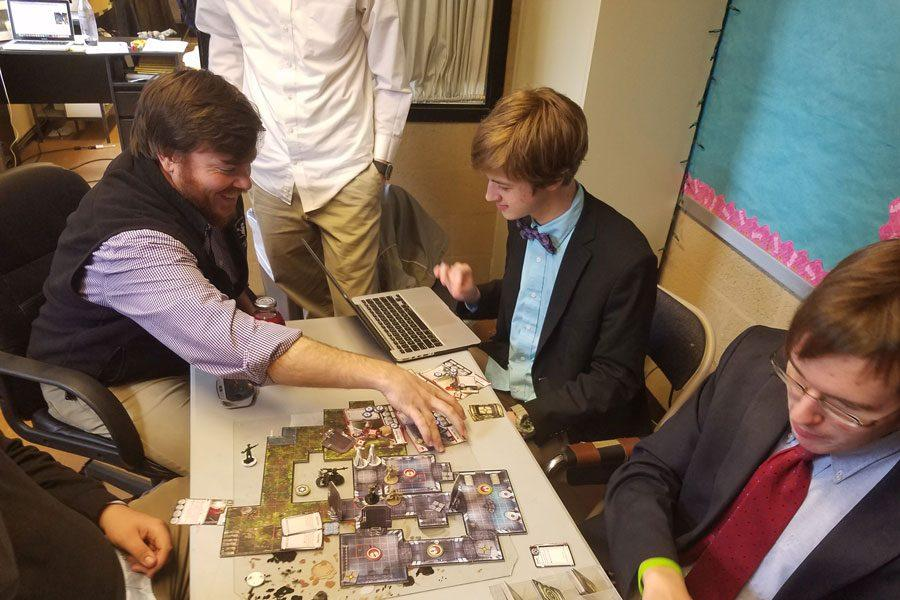 Strategic Games Club moderator Shane Lawler, along with sophomore Paul Capobianco and senior Darius Pirozzi, engages in a game of Star Wars Imperial Assault after school on March 20. The club meets every day after school, with Thursdays and Fridays being the most popular days.