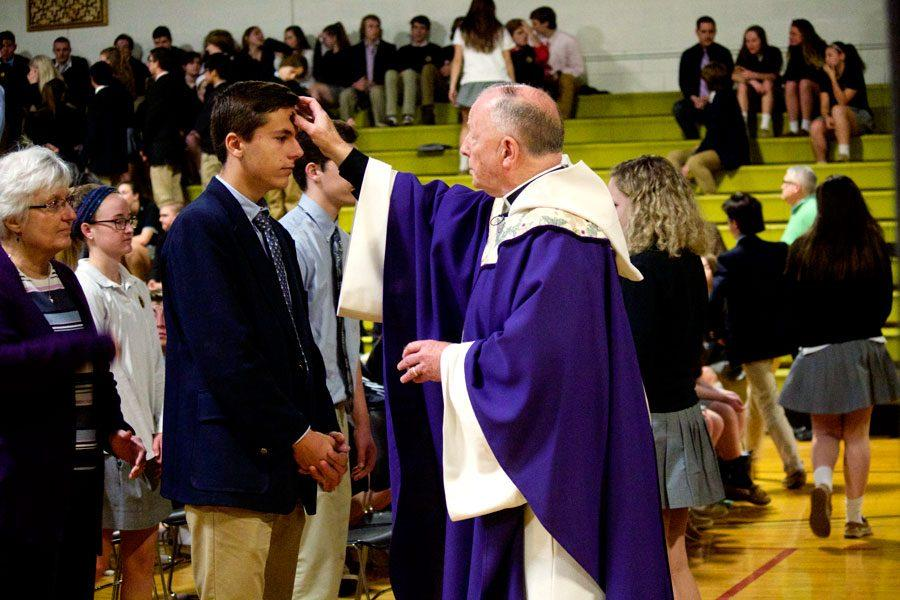 Father Steve Sutton makes the sign of the cross in ashes on senior Nick Hinke's forehead as part of the Ash Wednesday Mass tradition. Each year, JC holds an Ash Wednesday Mass for those who would like to receive ashes on the Holy Day of Obligation.