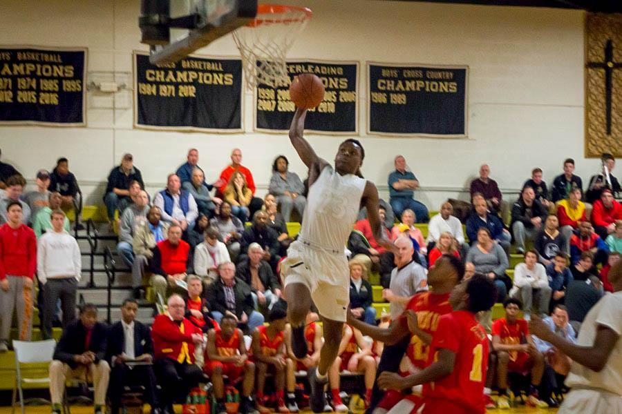 Junior guard Montez Mathis rises up for a dunk in the first quarter against Calvert Hall on Tuesday, Feb. 21. The men's varsity basketball team fell to Calvert Hall 78-84 in the MIAA A Conference Quarterfinals.