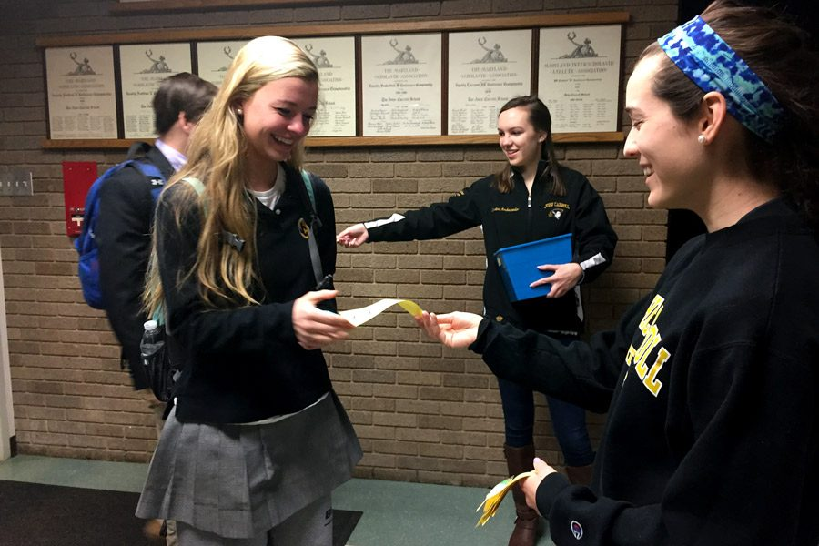 Junior Laura Amrhein hands sophomore Emily Schultz a piece of paper with a lifesaver attached to it as she walks into school on Wednesday, March 22. Members of Students Against Destructive Decisions (SADD) handed out lifesavers to remind students to make the right decisions by avoiding alcohol and drugs.