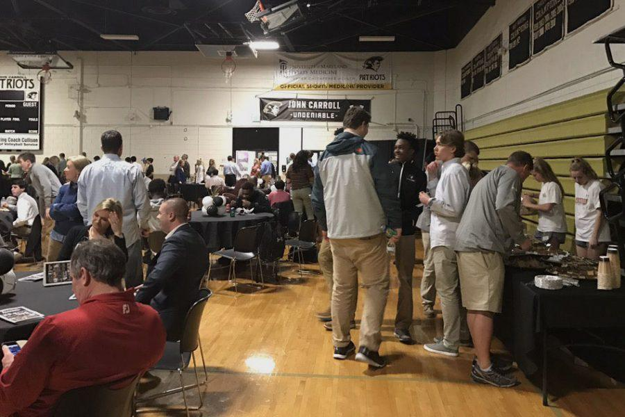 Athletes+and+their+parents+gather+around+the+dessert+table+at+the+Athletic+Banquet+for+fall+and+winter+sports.+The+banquet+was+held+on+Tuesday%2C+Feb.+29+in+the+Upper+Gym+and+celebrated+the+various+successes+of+teams+and+athletes.+
