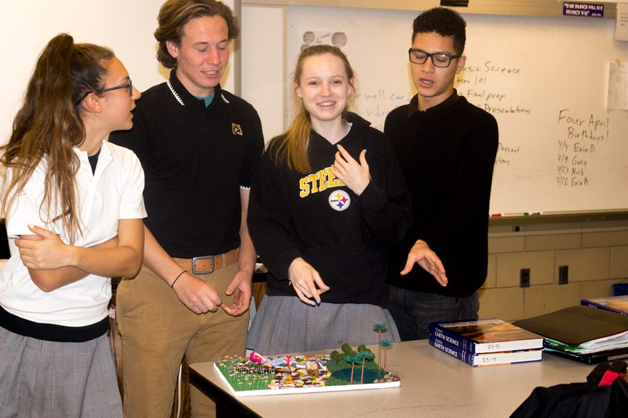 Junior Marissa DiFonso, senior Dylan Kidd, junior Reily Overend, and senior CJ Beteta (left to right) present their doll house crime scene to a Forensics class on Wednesday April 5. The class created a crime description and then made a dollhouse diorama to reflect the story.