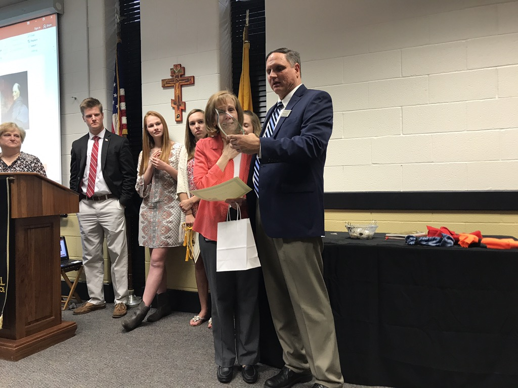 Campus Minister Gary Meyerl presents Ann Drummey with the Ann Drummey Service Award, honoring her years of service to the school and to the community. Drummey was surprised with this award at the Archbishop John Carroll Service Honors Society induction on Tuesday, March 28.