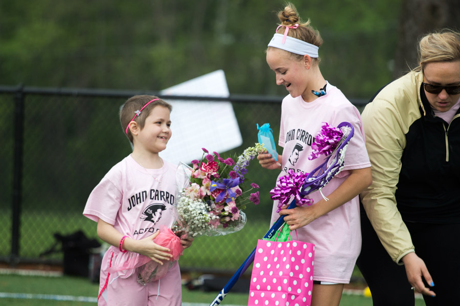 Senior Charlotte Haggerty and Mia Cochran exchange gifts before the varsity women's lacrosse game on April 27. For her Senior Project, Haggerty mentored Cochran, who was re-diagnosed with leukemia, and raised money during the lacrosse game to help the family pay for her treatment.