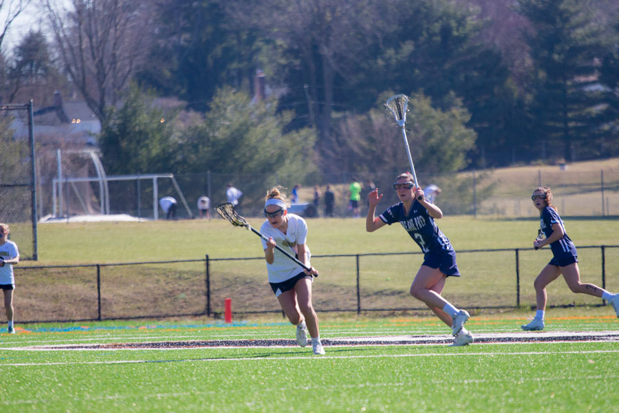 Senior Charlotte Haggerty cradles the ball with her stick as she runs past a defender from Notre Dame Prep. JC played NDP at home on Thursday, March 23 and lost 11-18.