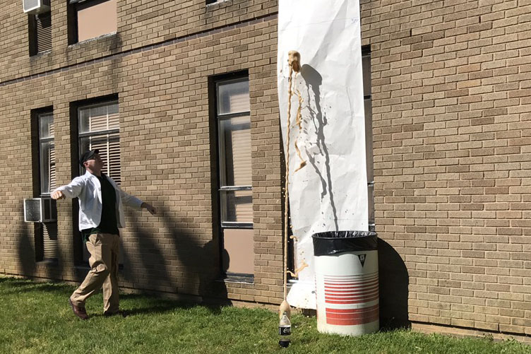Physics teacher Anthony Davidson watches as soda flies into the air. His Honors Physics class participated in an experiment on May 16 in order to discover the effect of putting Mentos in different types of soda.