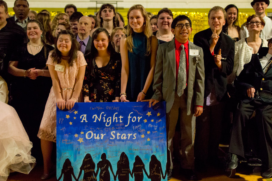 Senior Caroline Cooney poses with the special needs guests around the events poster. Cooney organized and directed the Special Needs Prom as her Senior Project and even received attention from the Catholic Review for her work.