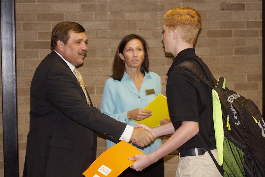 Interim President Steve DiBiagio shakes freshman Owen Collins's hand and speaks with Fine Arts Department Chair Lisa Collins.