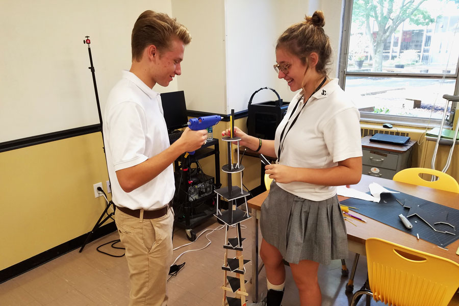 Senior Connor Kiss and sophomore Angela Kahoe work on a building for their Introduction to Engineering class on Sep. 21. Introduction to Engineering students are having a competition to build a structure that supports the most weight.