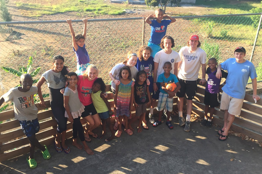 A coed group of students pose with children from Sandy Bay Lighthouse Ministry Children's Home on the annual Honduras service trip in 2016. While the trip was held for all females last year, it will be held for exclusively males this year.