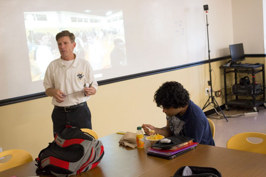 STEM Coordinator Michael Monaghan addresses his class while senior Sahil Menon eats his lunch. This year, STEM meetings were moved to lunch rather than being held during students' off mods.