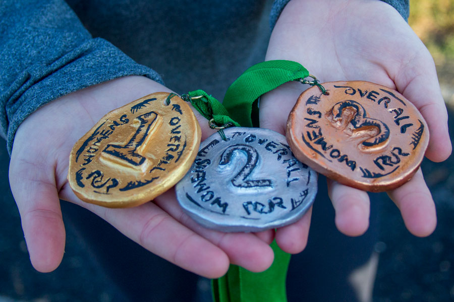 Senior Ashlee Kothenbeutel holds homemade medals awarded to top finishers in the 5k. The race was held on Oct. 21 and raised almost $800 to help refurbish the track.
