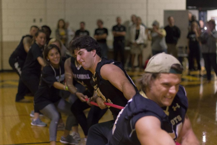 At the Homecoming Pep Rally, seniors Brett Raynor and Mike Gerace pull the rope during the juniors versus seniors bracket of tug-of-war. The team of seniors struggled to win but pulled through at the end, securing the victory for the senior class.