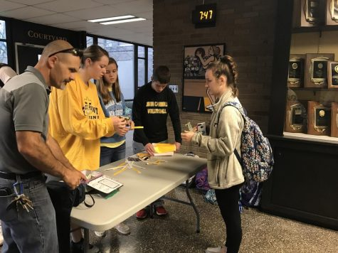 Freshman Sophia Parr buys a bracelet for the dress down day on Friday, Sept. 29. The dress down day was hosted by the Fellowship of Christian Athletes to raise money for a new Patriot mascot. Social studies teacher Jake Hollin, along with juniors (left to right) Kirstin Huggins, Sarah Spaeth, and Matt Smidt, sold bracelets.
