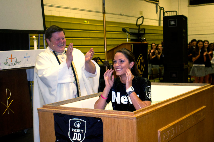 Ashley Schwartz rises from a baptismal pool on Friday, April 28 after declaring her Catholic faith at the End of the Year Mass during her junior year. While many share in Schwartz's Catholic faith, 35 percent of students practice a religion other than Catholicism, according to a survey sent out by The Patriot.