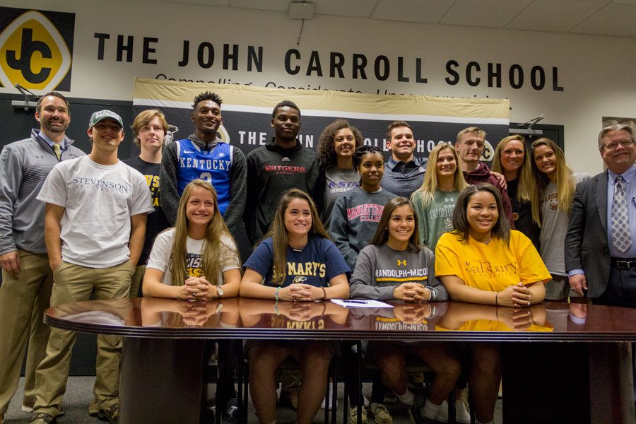 Athletic Director Steve Teter, seniors Luke Ensor, Nick Collier, Immanuel Quickley, Montez Mathis, Savannah Simmons, Myah Savage, Ryan Archibald, Meghan Sheehan, RJ Price, Administrative Assistant Abbey Swift, senior Ashley Schwartz, Principal Tom Durkin, seniors Molly Lynch, Sammi Edwards, Callie Courtalis and Nikki Hunter pose after the College Signing Breakfast on Thursday, Nov. 9.