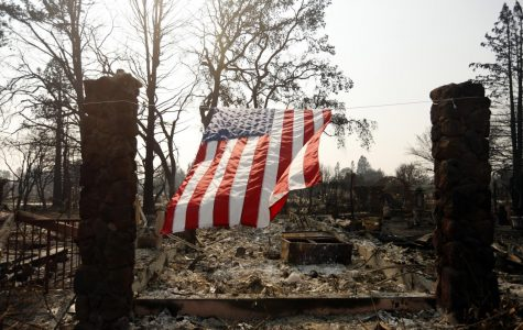 A U.S. flag hangs from the remnants of a fire-ravaged home on Willowview Court in the Coffee Park neighborhood of Santa Rosa, Calif. on Wednesday, Oct. 18, 2017.