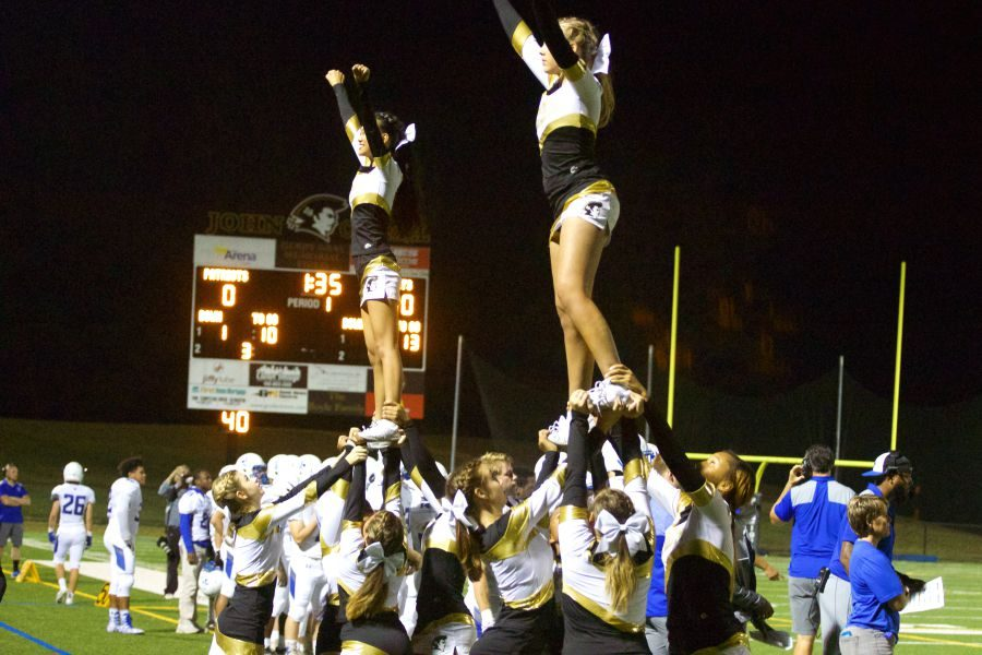 Members+of+the+cheerleading+team+perform+a+stunt+during+the+Homecoming+game+on+Friday%2C+Oct.+6.+This+season%2C+the+team+was+much+smaller+than+previous+squads+and+only+had+two+stunt+groups.