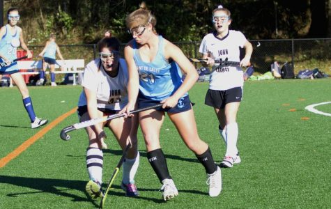 Senior center forward Sammi Edwards fights for the ball against a Mount de Sales player with left wing Kendall Rittmeyer following behind. Monday, Oct. 30 marked the end of the field hockey season with a 2-0 IAAM quarterfinal loss to Mount de Sales.