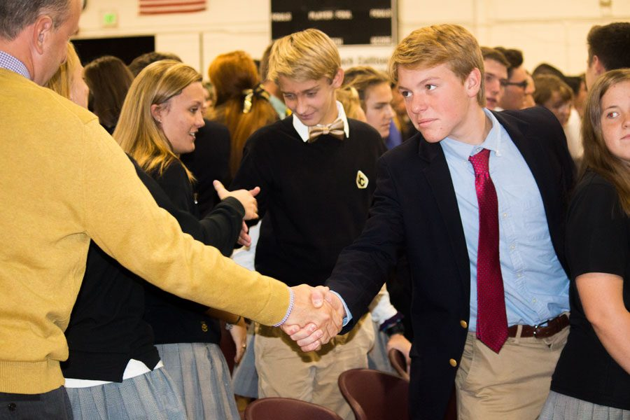 Sophomore Garrett Smith offers a sign of peace to English teacher Matthew Blair during Mass. The All Saints' Day Mass was held on Wednesday, Nov. 1 in the upper gym.