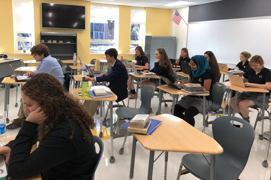 Students in AP Language and Composition work on an analysis essay. The class moved to the model classroom from The Patriot Room to accommodate their large class size this year.