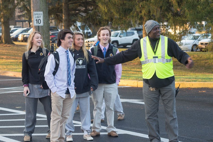 Member of the Facilities Management Department John Wilkie directs juniors Taylor Umbarger, Kiersten Euler, Jordan Remeto, and senior Auggie Van Dalsum on their walk from the student lot to school on the morning of Friday, Dec 1. The crossing guard is just one solution to many problems that remain.