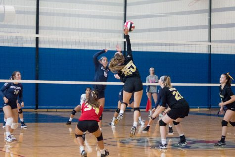 Junior outside hitter Mallory Lyon spikes the ball over the net during the women